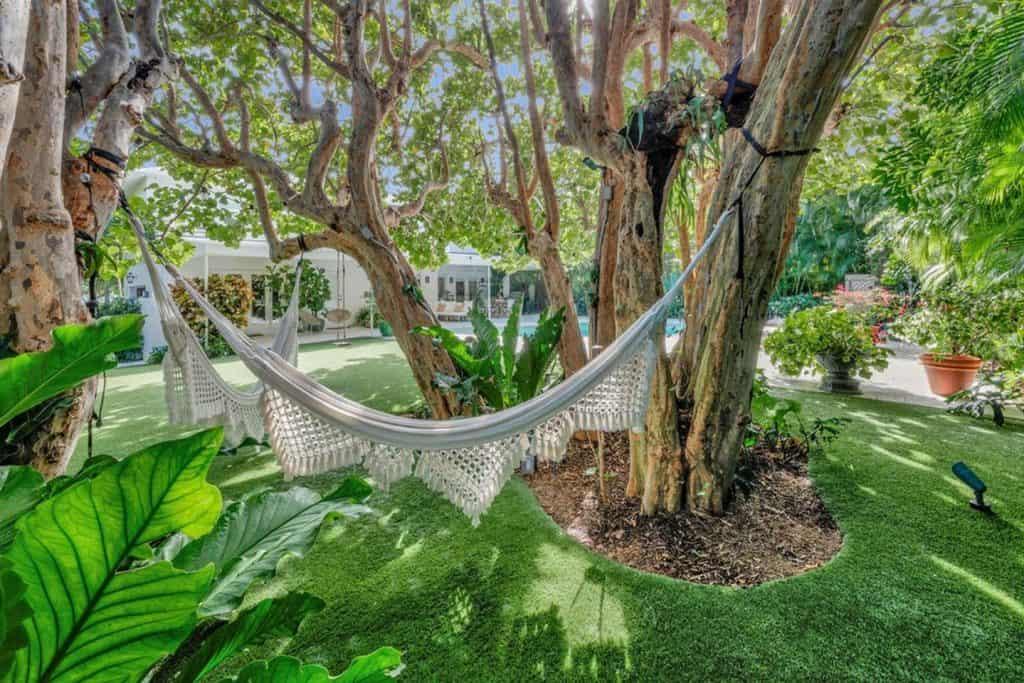 Bohemian Elegant Luxury Paradise AirBnb Beach House Decor - hammock between trees in tropic oasis
