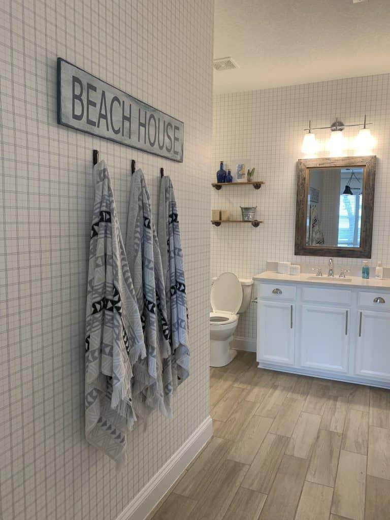 Beach Walk House Tour - Coastal Chic Design and Decor Ideas - bathroom with beach house sign