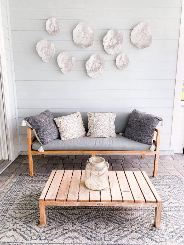 Outdoor covered patio with teak couch and gray cushions