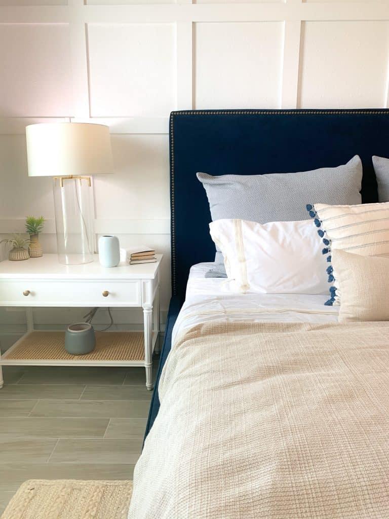 Navy blue upholstered bed frame, burlap bedding, gray pillows, white side table