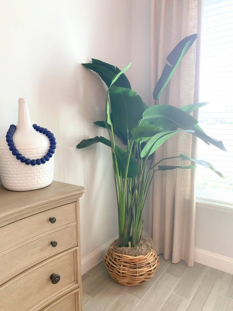 Master bedroom corner styling with planter and white vase