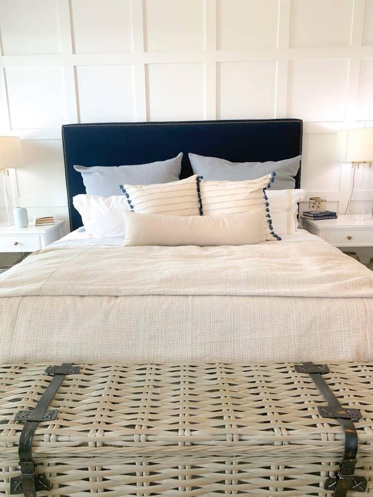 Master bedroom with navy blue upholstered bed frame and coastal neutral bedding
