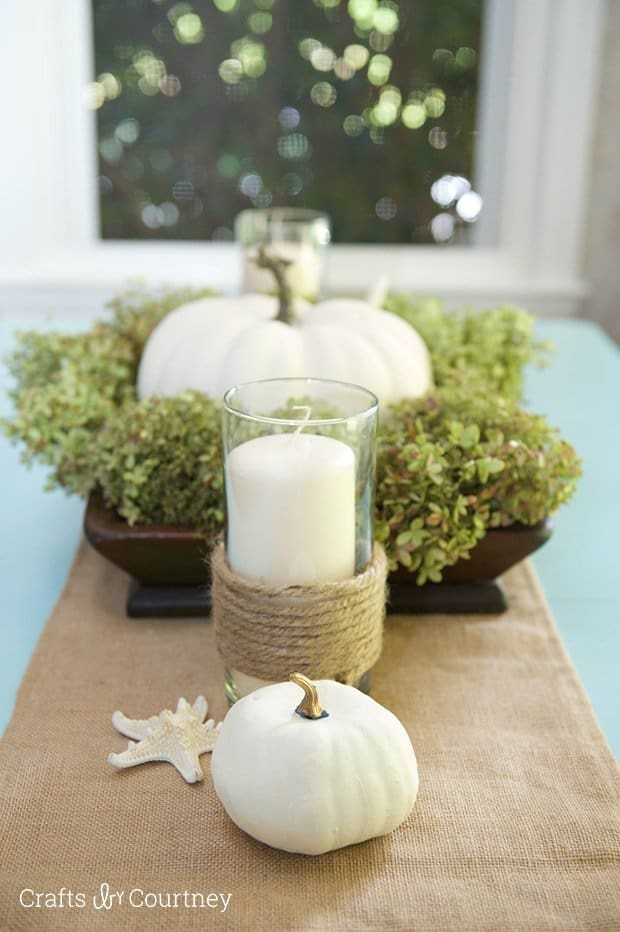 Coastal Fall Tablescape - White pumpkin centerpiece on this fall table setting design with blue tablecloth, burlap table runner, candles in glass jars