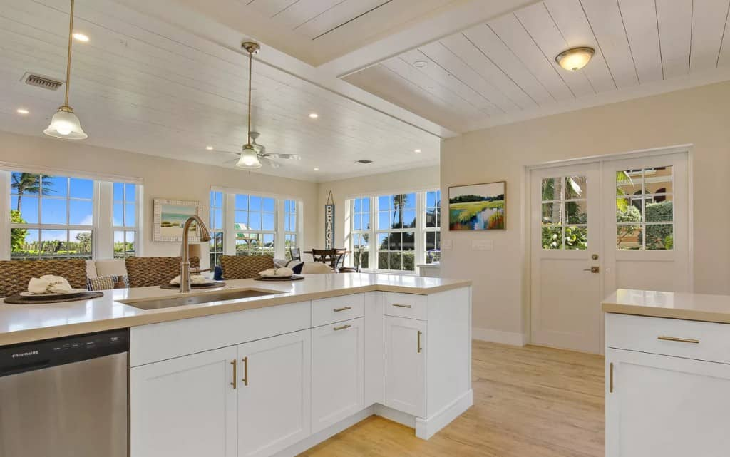 White Coastal Neutral Kitchen!  Shiplap on the ceilings, light wood floors, brass hardware on white cabinets