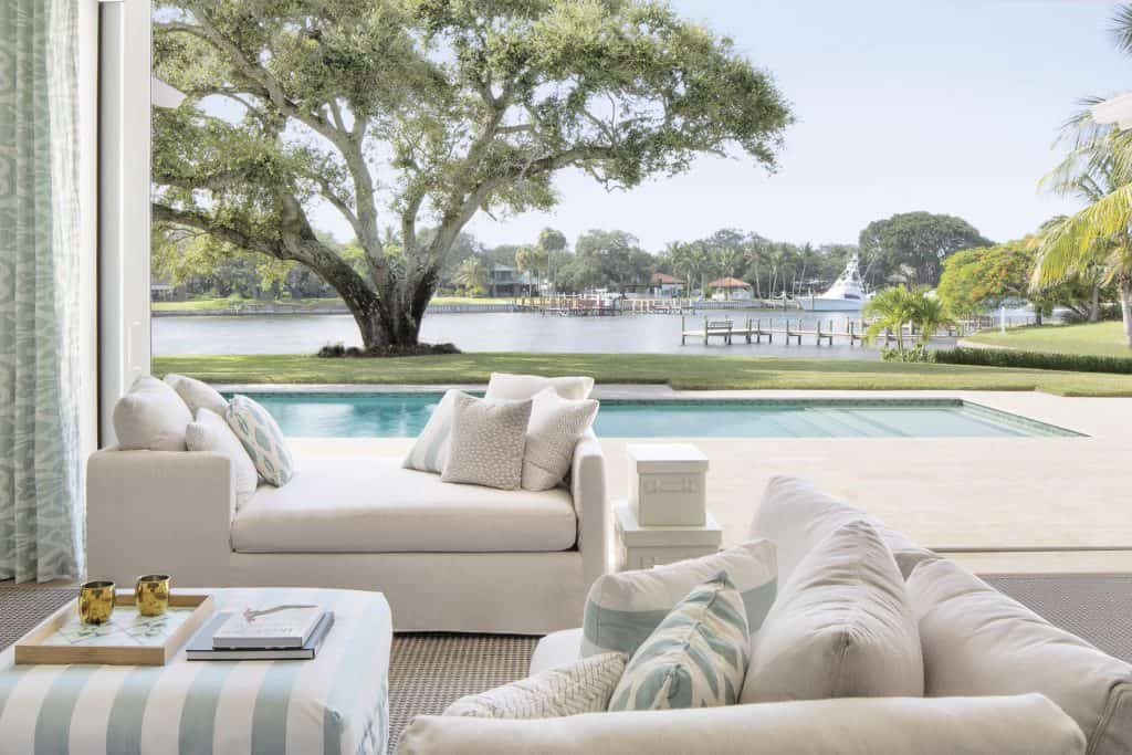 Coastal Living Room Open To The Outdoors - View Of Pool and Waterway Dock - Coastal Calm Home Design With Amazing Relaxed Beach Décor Ideas