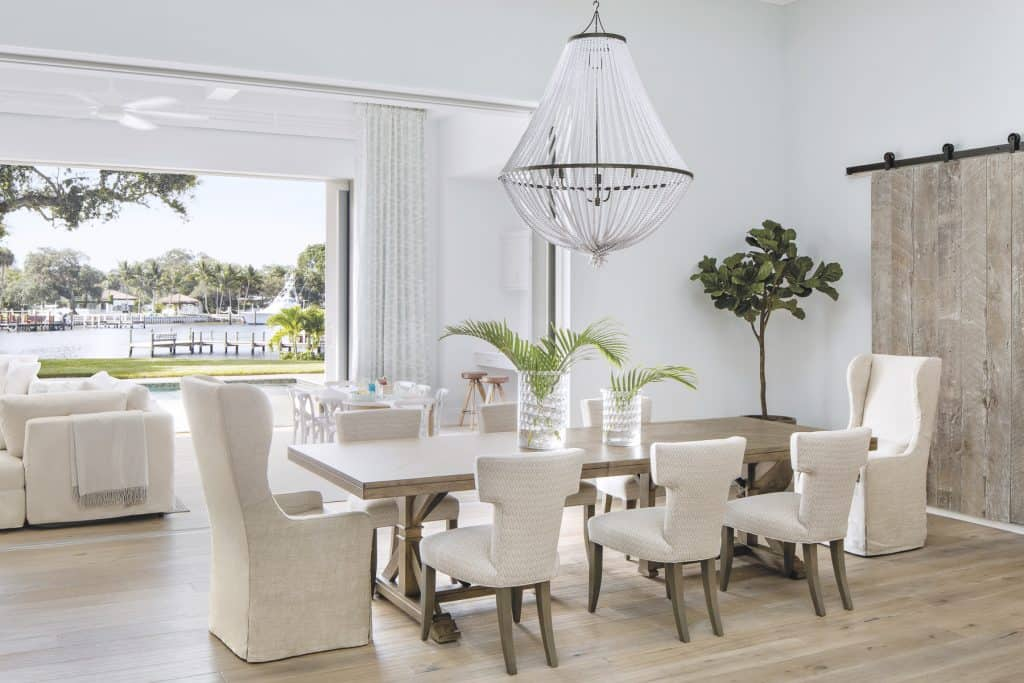 Coastal Farmhouse Dining Table With Comfortable White Upholstered Chairs - A Barnwood Door Feature - Coastal Calm Home Design With Amazing Relaxed Beach Décor Ideas
