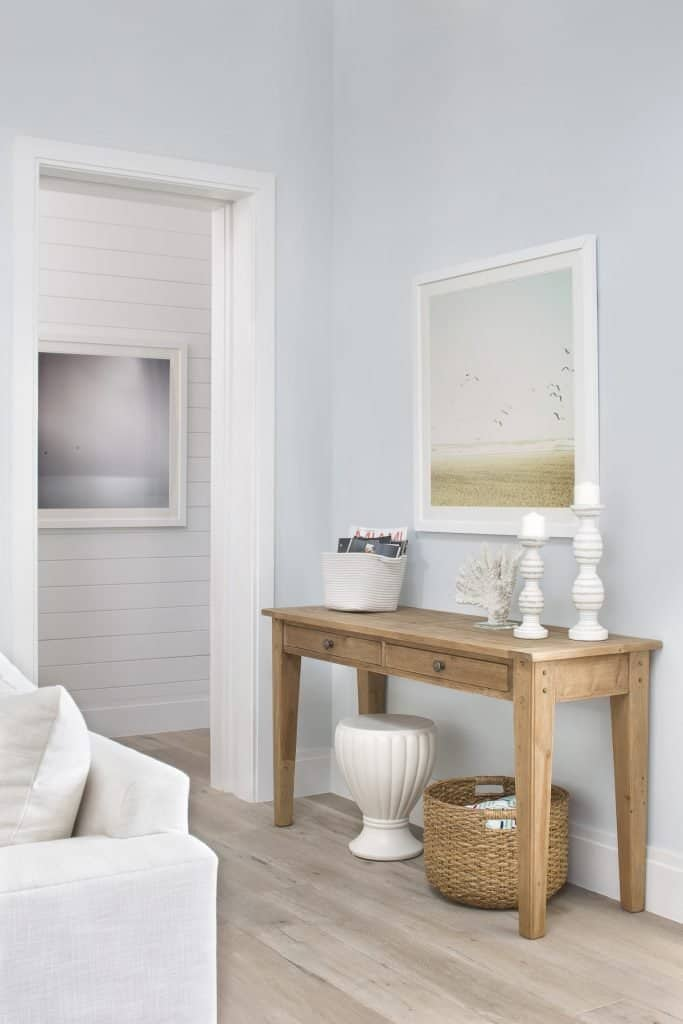 Simple Coastal Console Table Style - Wicker Basket and Neutral Beach Framed Art - Coastal Calm Home Design With Amazing Relaxed Beach Décor Ideas
