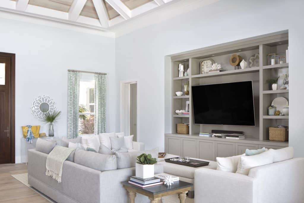 Family Room With Built In Shelving Around TV - Gray Comfy Couches For Seating - Coffee Table Plush Ottoman - Coastal Calm Home Design With Amazing Relaxed Beach Décor Ideas