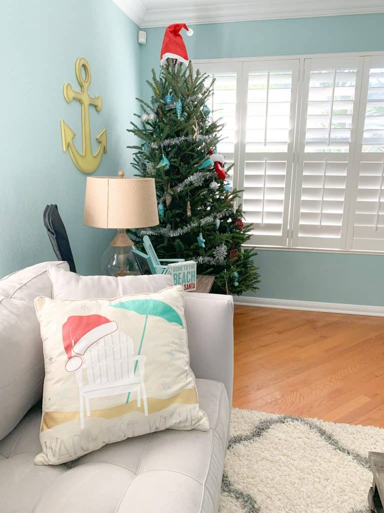 Florida home with classic Christmas tree - coastal blue ornaments, silver garland, gone to the beach love santa sign