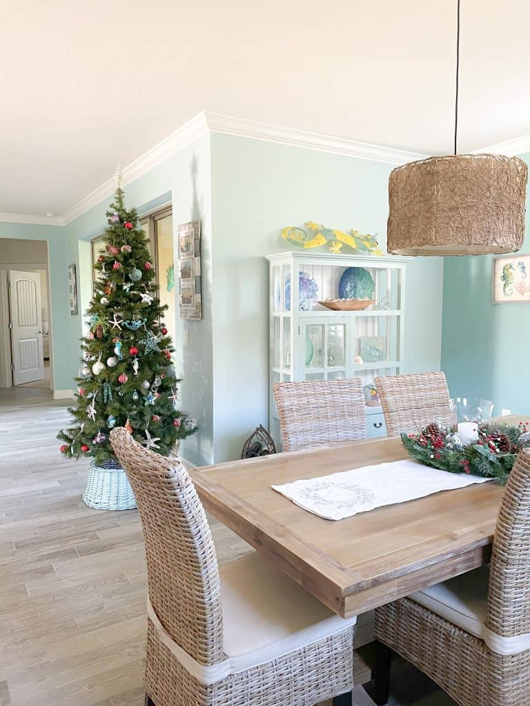 Dining room table with neutral holiday decor, coastal colors, light wood dining table, and wicker chairs