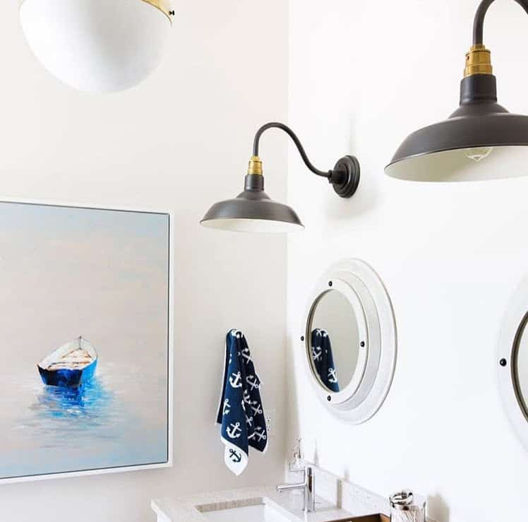 Nautical bathroom decor and design - white walls, white circular mirrors, rustic black light fixtures