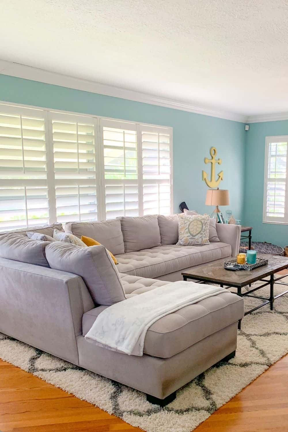 Coastal living room with beachy blue walls and gray couch - yellow accents - living room color ideas