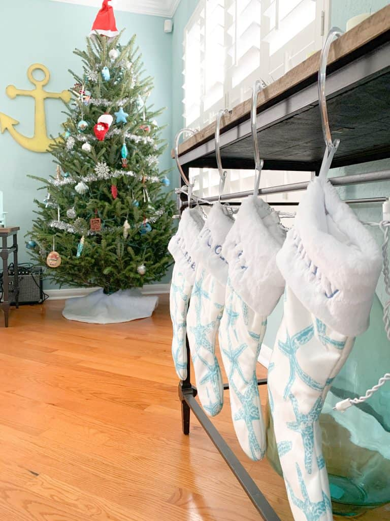 Classic coastal Christmas tree with Santa hat, beach blue ornaments, silver garland