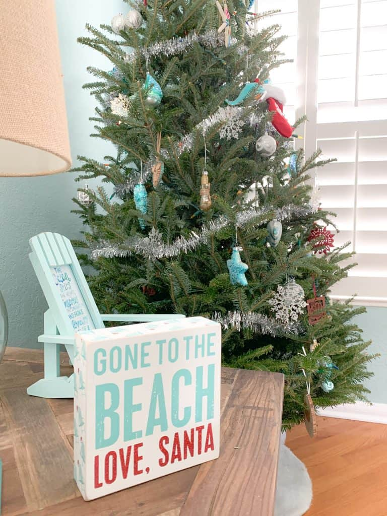 Coastal Christmas tree with blue coastal ornaments, silver garland, pops of red.