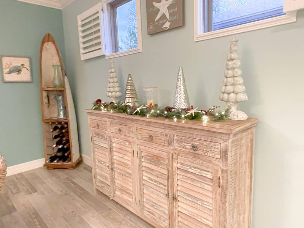 Coastal dining room decorated for Christmas with silver, blue, and red - beautiful light wood sideboard console with greenery and silver accent tree decor