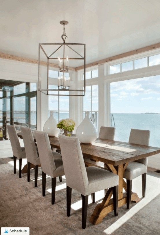 Coastal style dining room with beautiful extra long medium wood toned farmhouse table