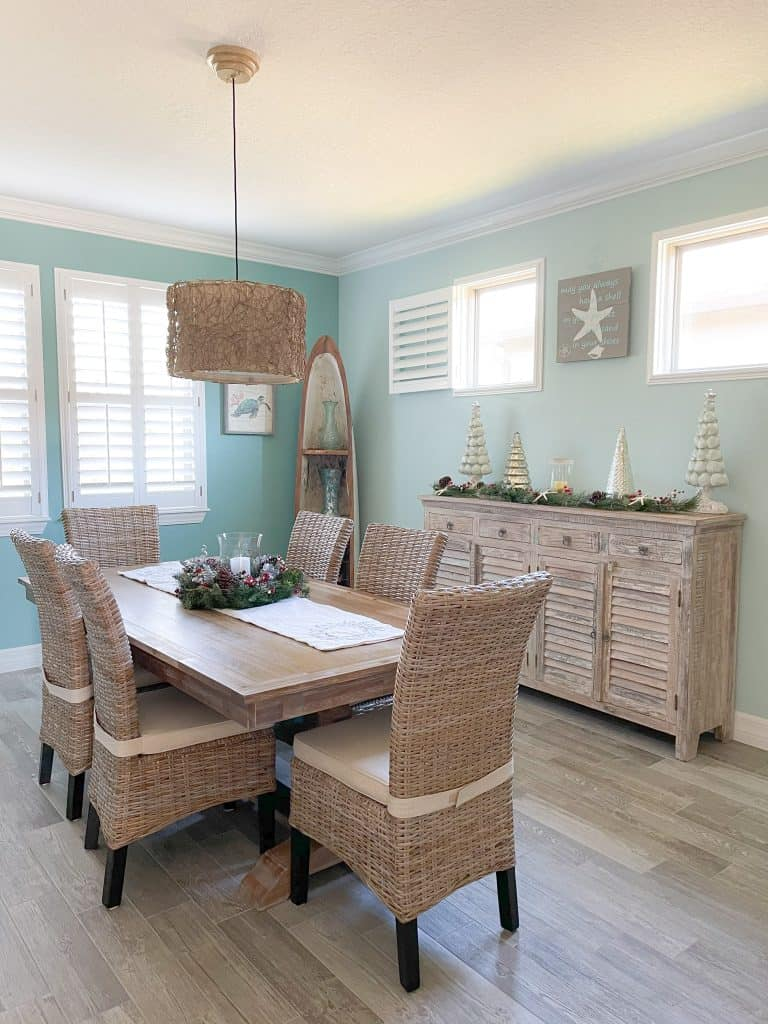 Elegant Coastal Holiday Christmas Dining Room Table with greenery centerpiece and candle - light wood side board with neutral christmas tree decor pieces