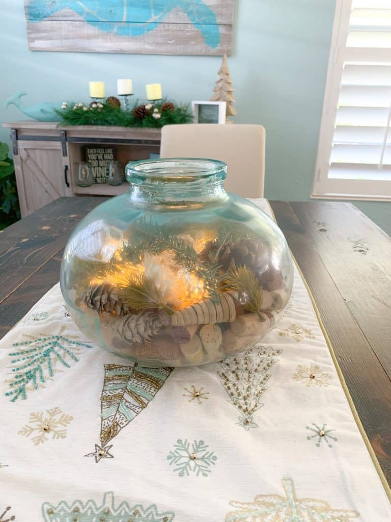 A Unique Sea Glass Table Centerpiece with wine corks, pine garland, pine cones, and twinkle fairy lights