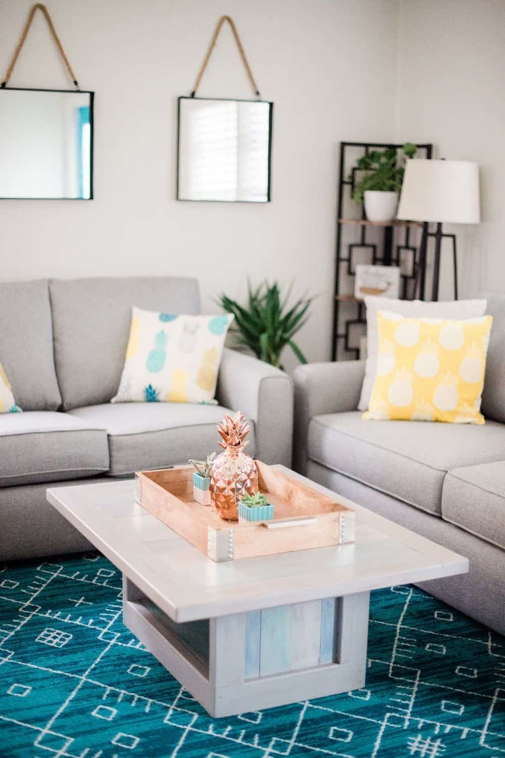Beach Bungalow Living Room With Gray Couches and Yellow Pineapple Pillows and bold blue rug