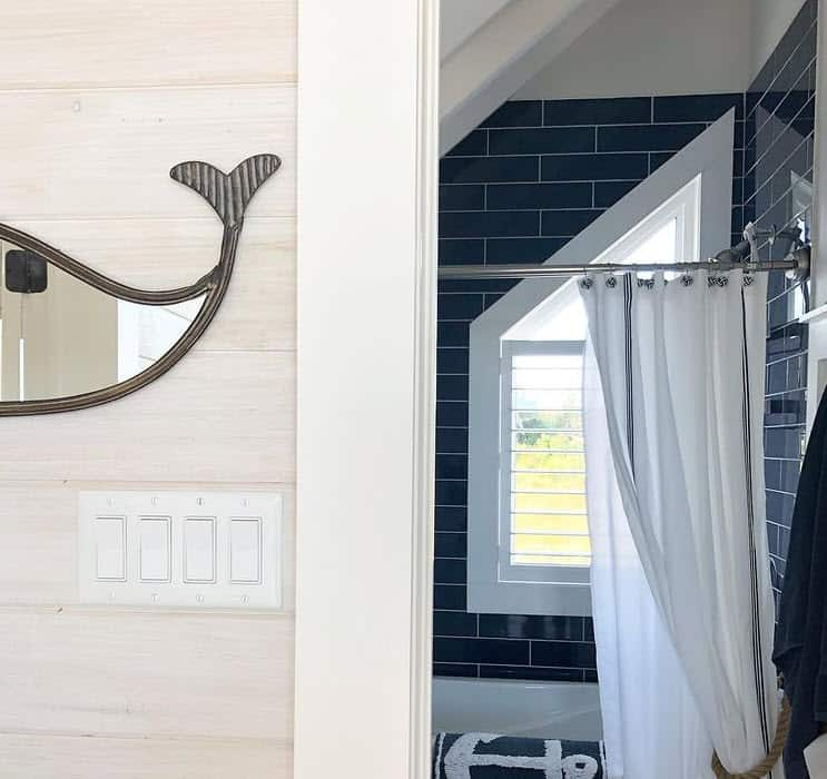 Navy blue subway tile bathroom with a whale mirror in this nautical bathroom design