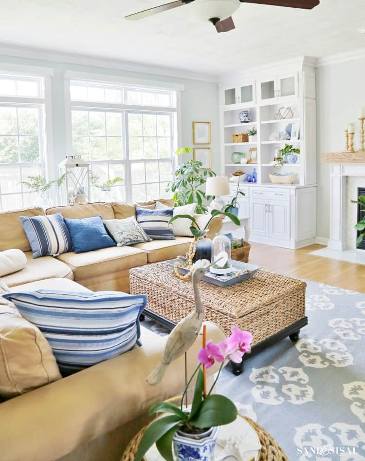Summer blues living room by sand and sisal.   he color scheme is a beauty with muted blue tones, a nice airy shade of green on the wall, cream colored couch, and blue accent pillows.