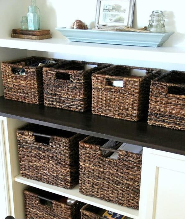 Built in open cabinets with brown baskets for organized storage