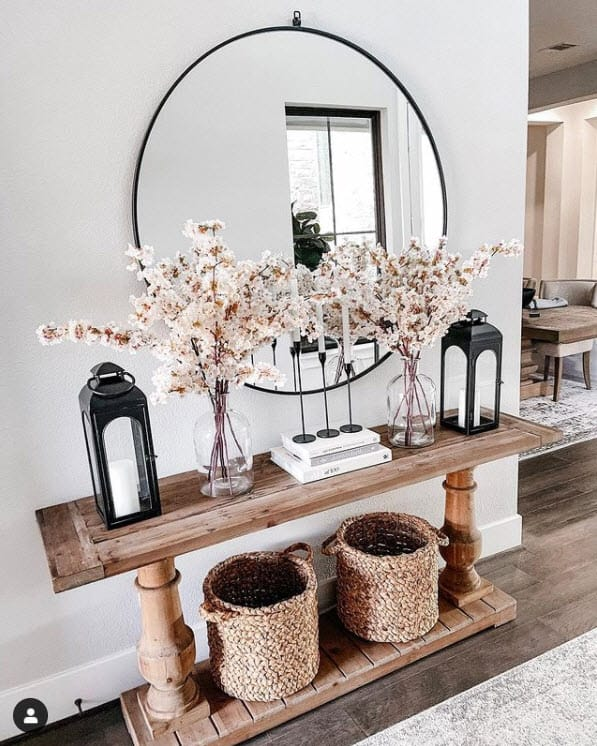 Entry hallway with farmhouse style console table and large black circular mirror - Baskets underneath for storage and organization
