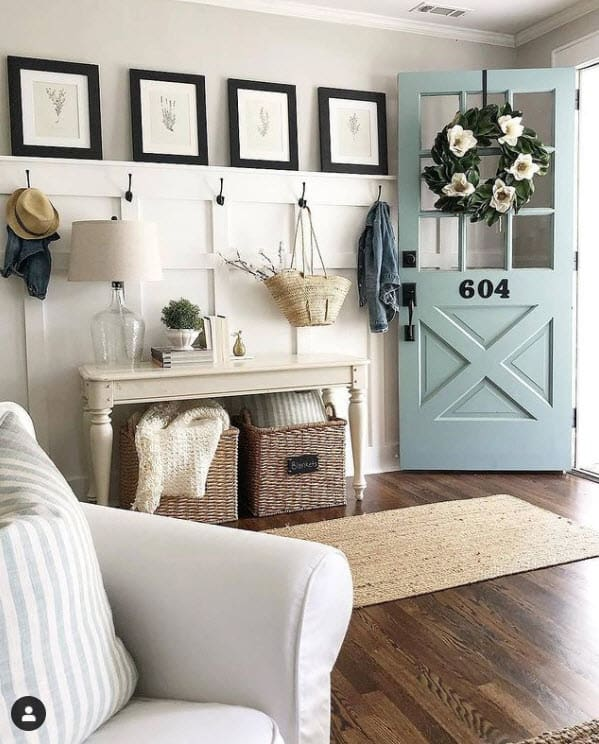 Entryway with basket storage under console table - A mint green front door is next to the farmhouse style entry table