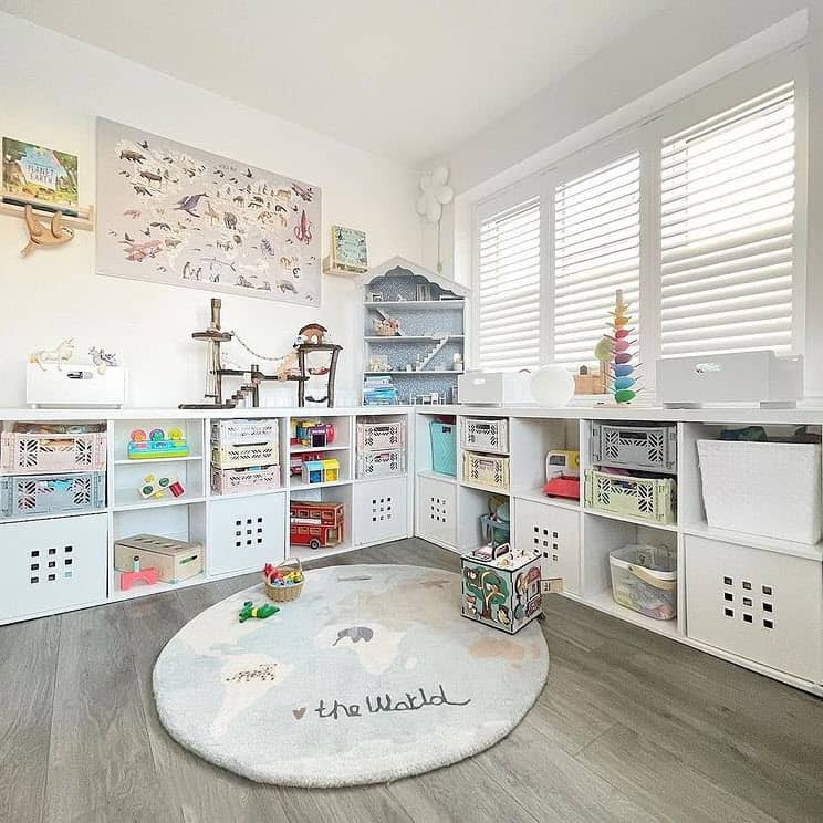 Kids playroom with white open shelving.  Baskets are used to organize and declutter the space.