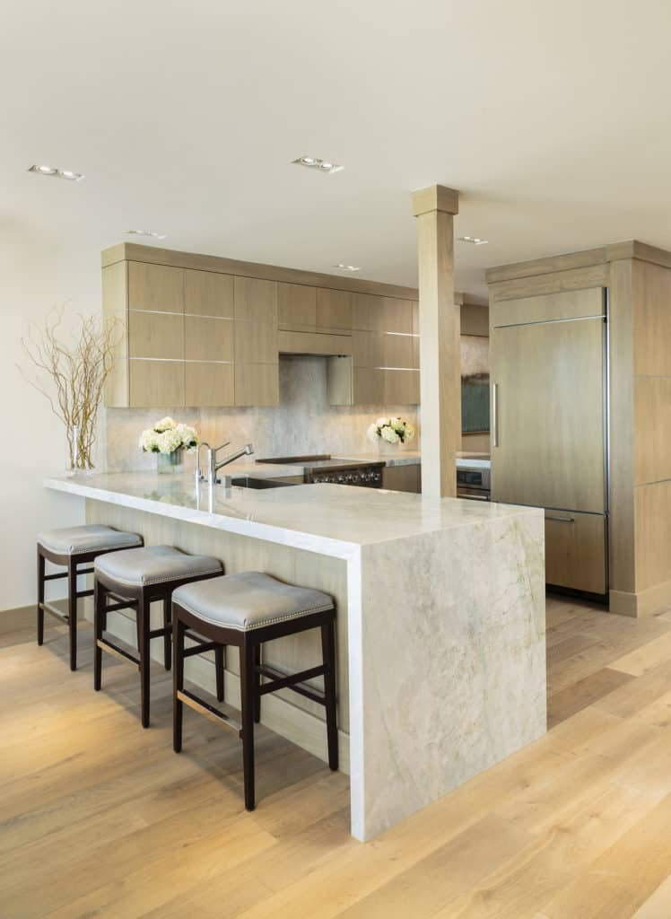 Low profile bar stools at a white kitchen island peninsula.  Tan modern cabinets and neutral coastal backsplash in this kitchen