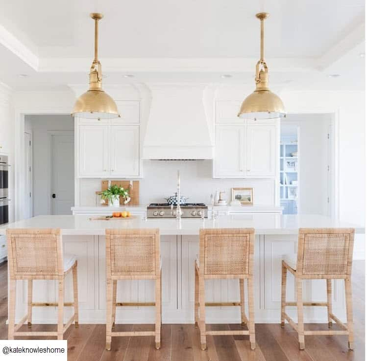 White kitchen with large island and natural basket weave bar stools