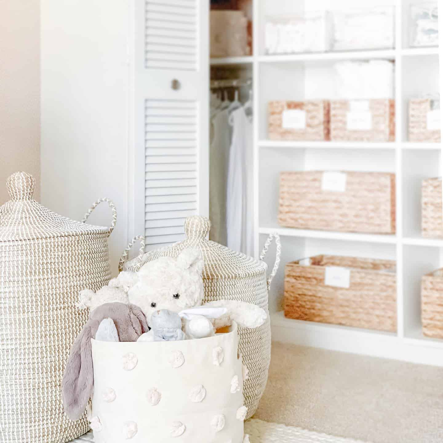 Baby bedroom with serena and lily storage baskets.  Closet with built in shelving and wicker baskets for organizing on the shelves.