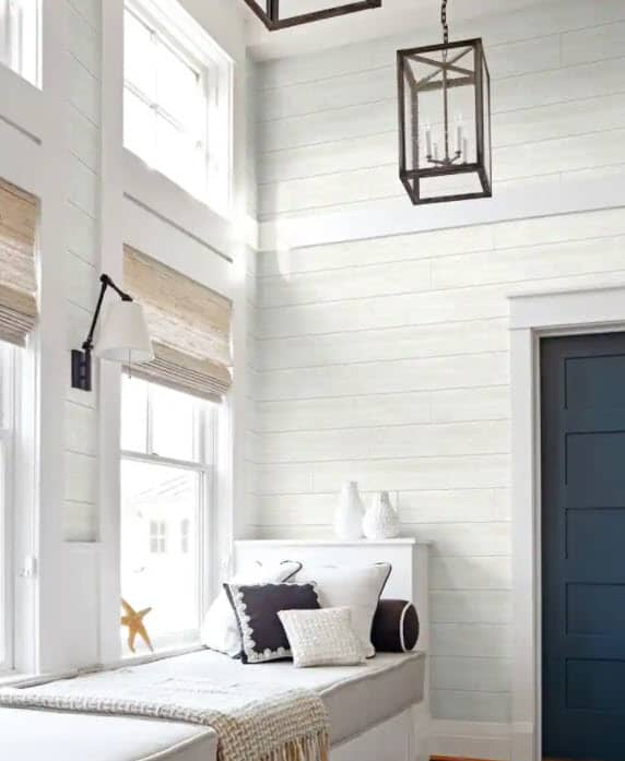 Nautical looking built in window bench with a navy blue door and shiplap accent wall - using shiplap peel and stick wallpaper