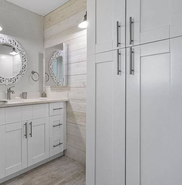 White bathroom with light wood accent wall