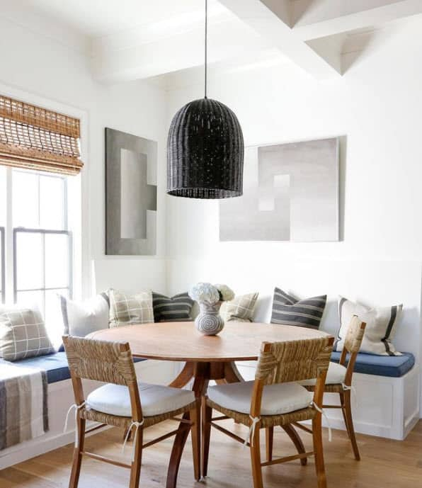 Black Headlands Bell Pendant by Serena and Lily over round dining table nook with built in bench seating