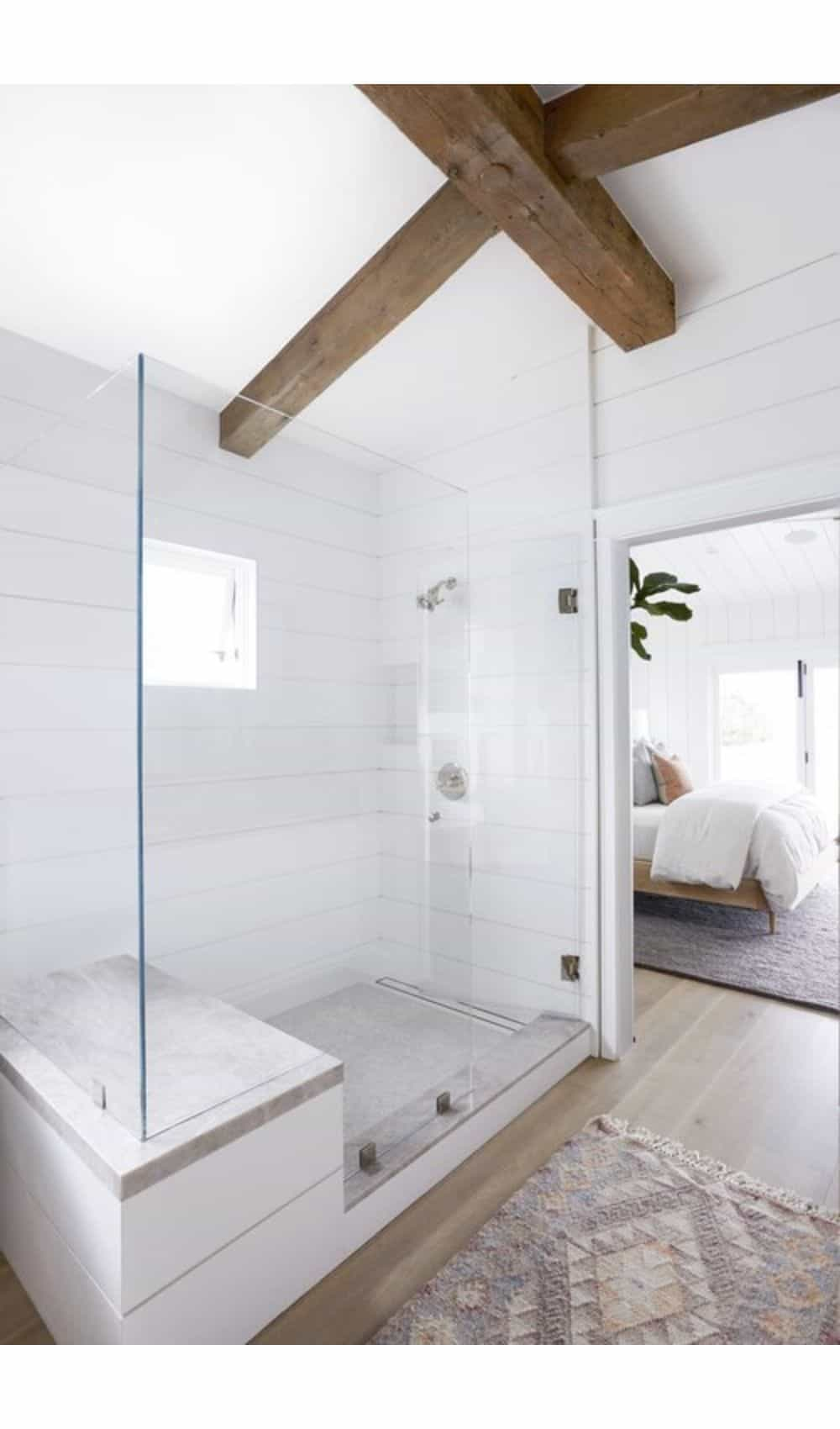 Large glass shower in master bathroom - white shiplap walls, marble tile, and wood beams on the ceiling
