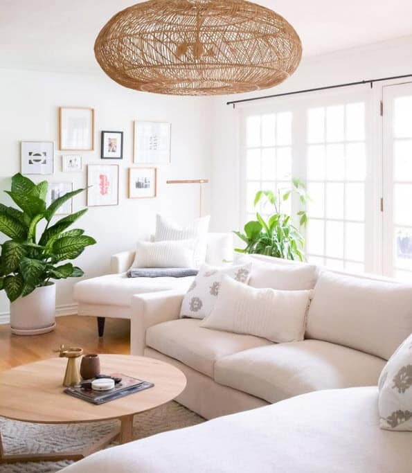 Airy living room with white sectional, rattan round light fixture, cozy corner chair, air plants for a boho feel