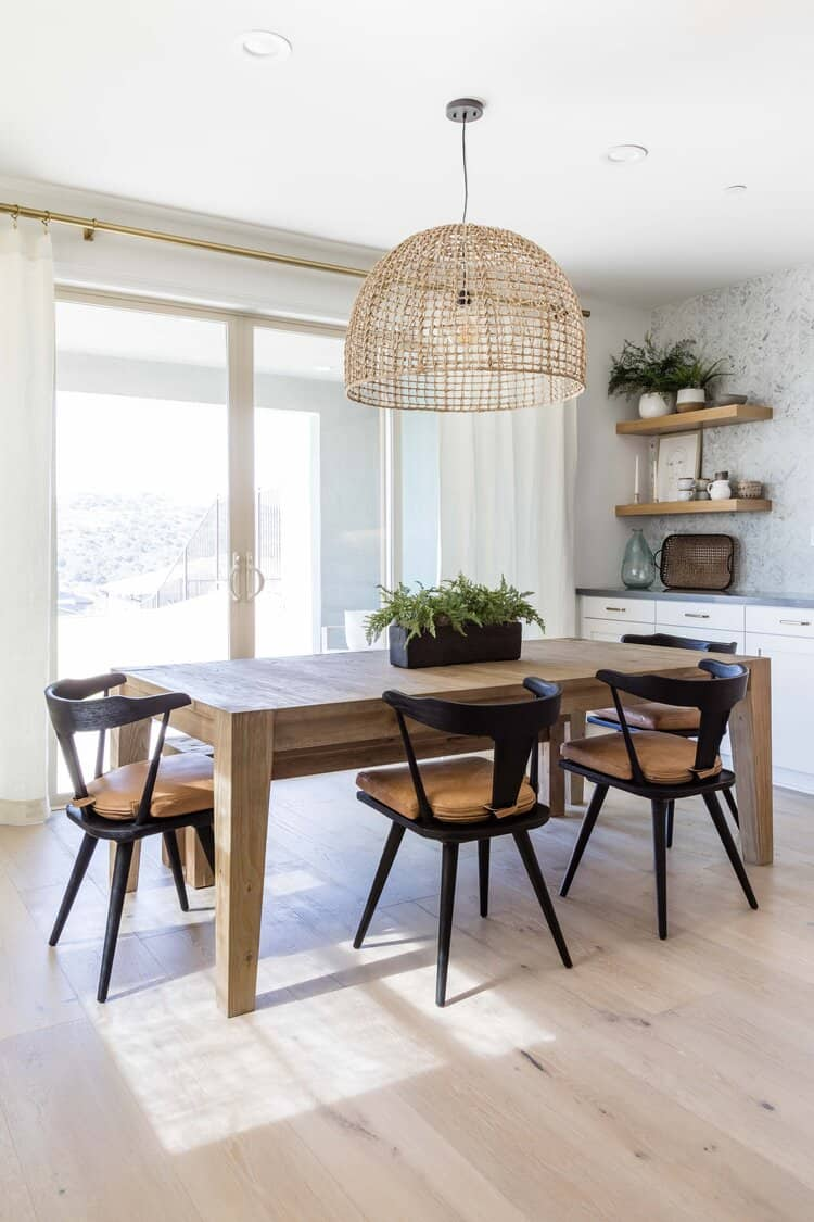 Large wicker rattan hanging light over wood kitchen table.  Simple ocean green glass accents