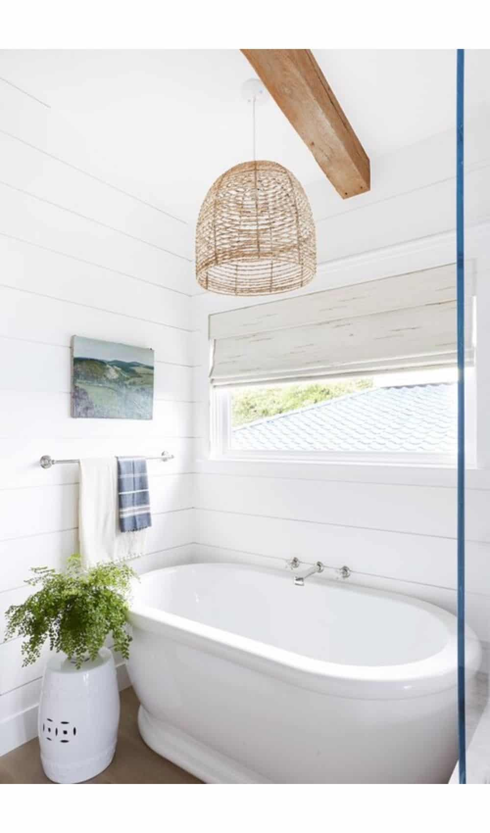 bathroom corner window with beautiful white bathtub, wicker rattan pendant light