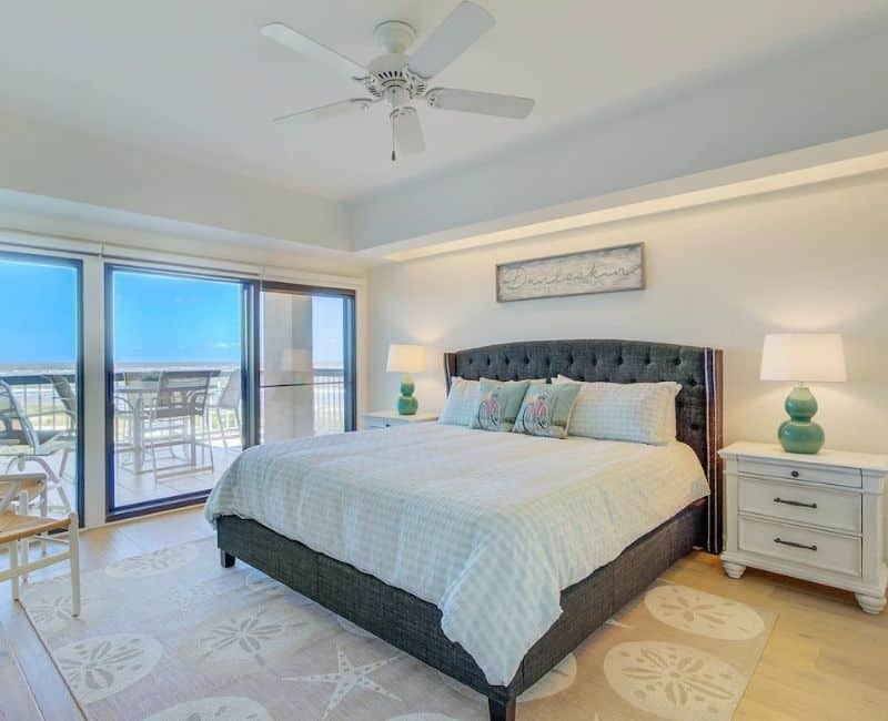 Master Bedroom Oceanfront Condo - Dark Gray Upholstered Headboard, sand colored area rug with shells, walk out balcony with ocean views