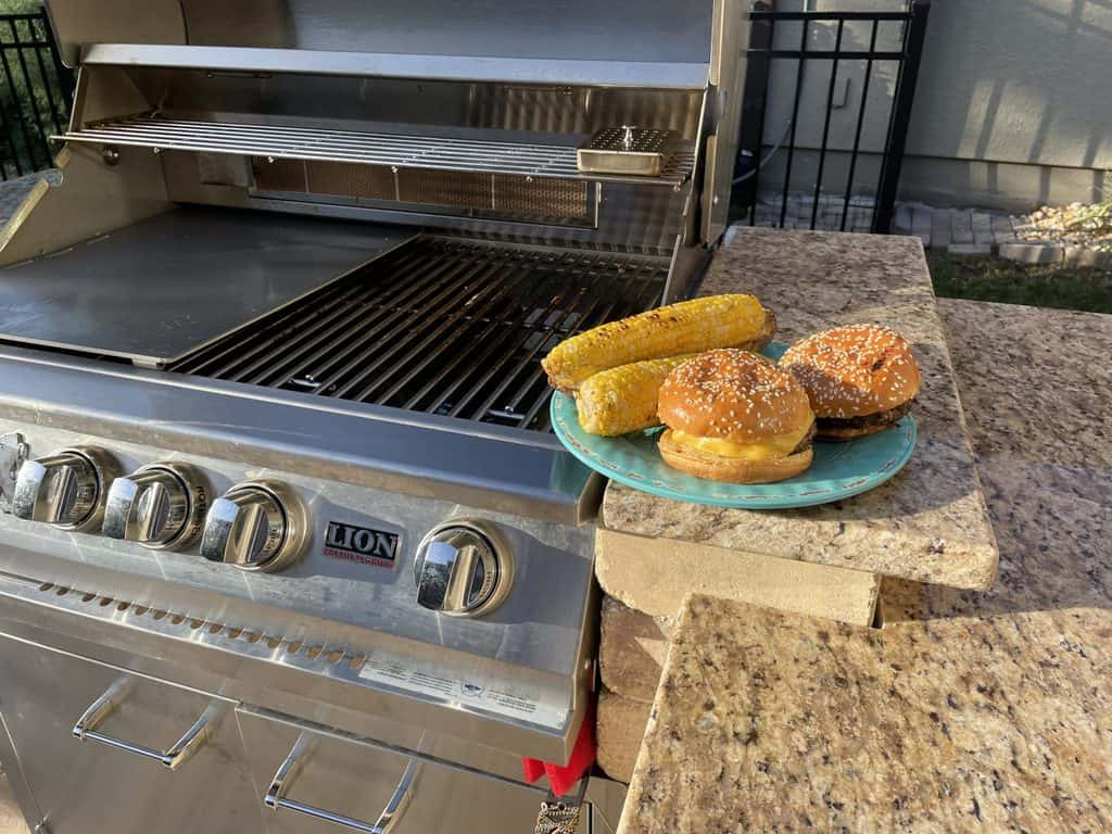 BBQ grill with burgers and corn