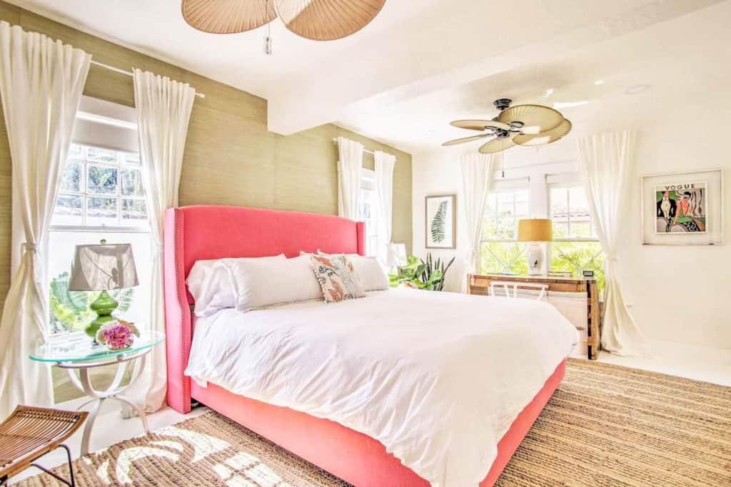 airbnb bedroom coral headboard green grasscloth wallpaper