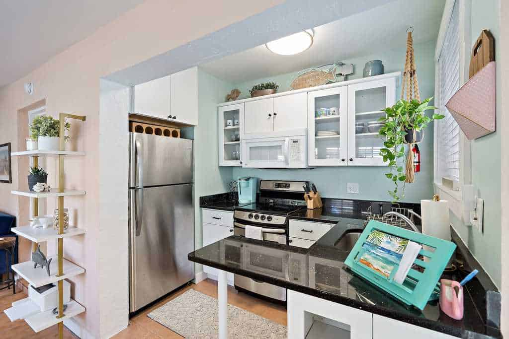tiny white and seafoam green airbnb kitchen
